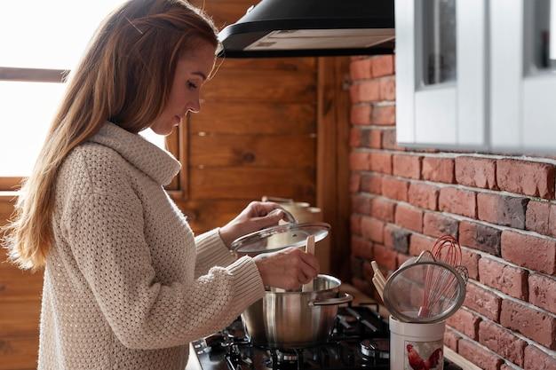 Coup moyen femme cuisinant à la maison