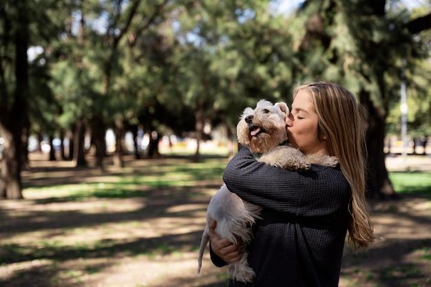 Coup moyen femme embrassant un chien