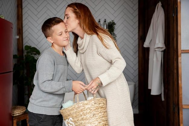 Coup moyen femme embrassant un enfant sur la tête