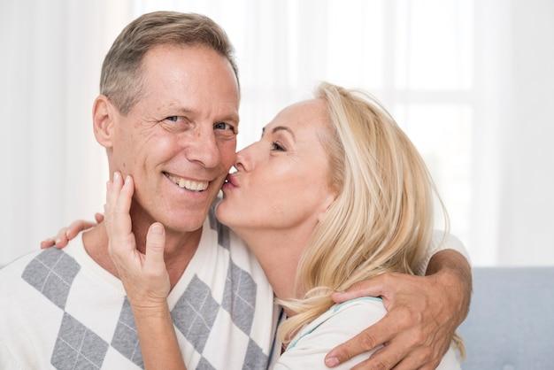 Coup moyen femme embrassant un homme sur la joue