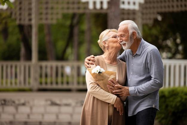 Coup moyen femme embrassant l'homme sur la joue