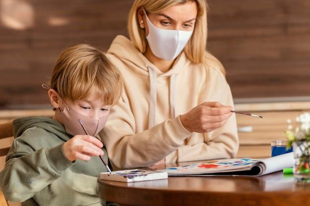 Coup moyen femme et enfant tenant des pinceaux