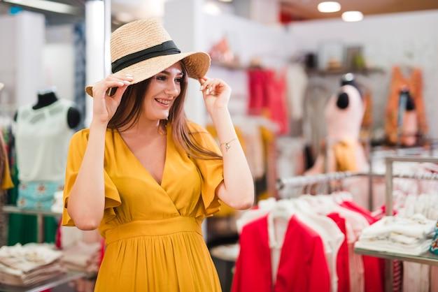 Coup moyen femme essayant un chapeau
