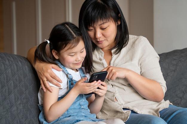 Coup moyen femme et fille avec téléphone