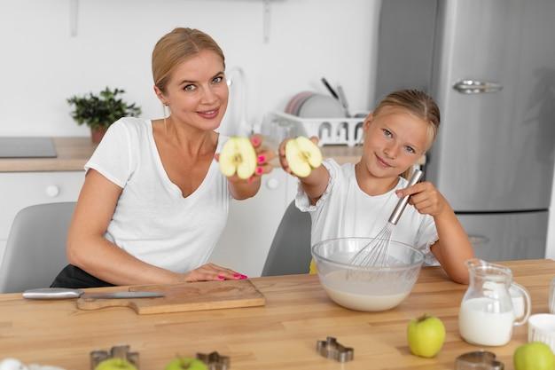 Coup moyen femme et fille tenant des pommes