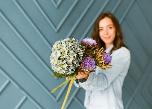 Coup moyen femme floue tenant beau bouquet