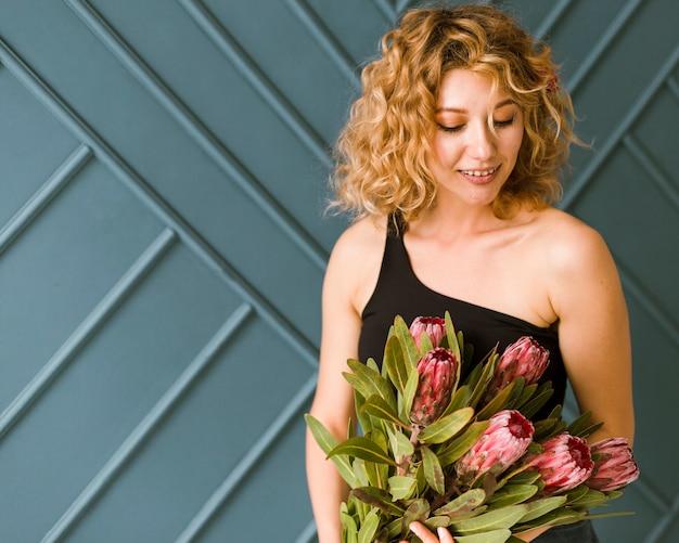 Coup moyen femme heureuse avec bouquet à l'intérieur