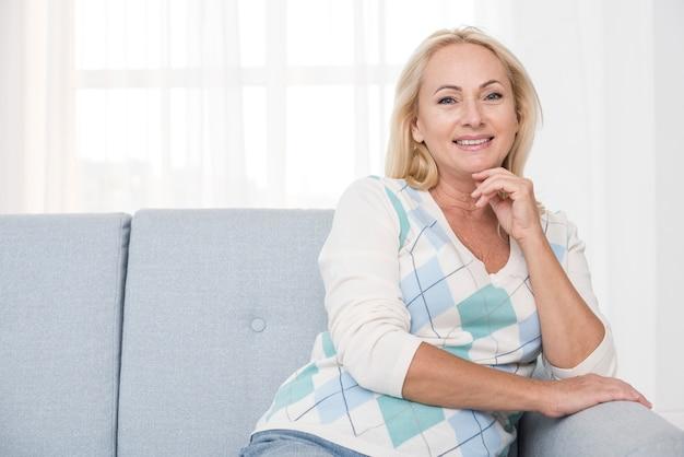 Coup moyen femme heureuse sur le canapé posant