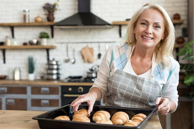 Coup moyen femme heureuse avec des croissants