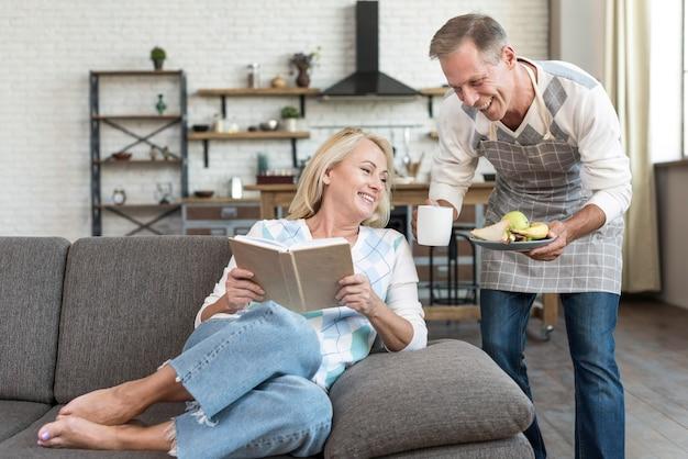 Coup moyen femme heureuse lisant sur le canapé