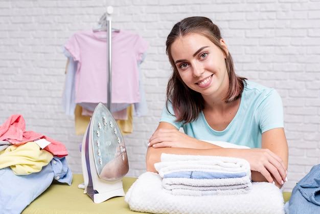 Coup moyen femme heureuse près de vêtements pliés
