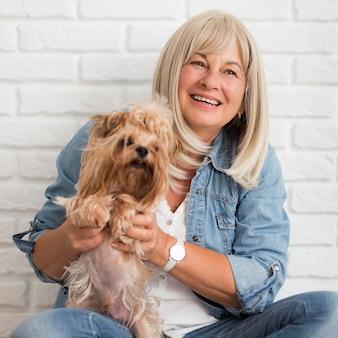 Coup moyen femme heureuse tenant un chien