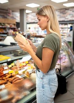 Coup moyen femme lisant l'étiquette du produit