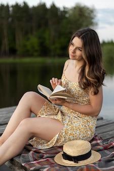Coup moyen femme lisant à l'extérieur