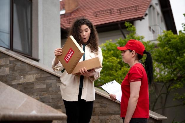 Coup moyen femme livrant un pack à la maison