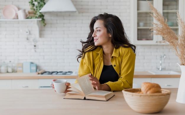 Coup moyen femme avec livre et tasse de café