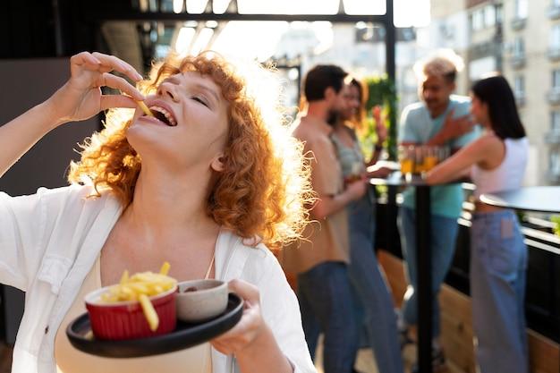 Coup moyen femme mangeant des frites