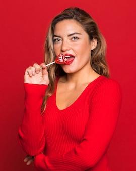 Coup moyen femme mangeant une sucette
