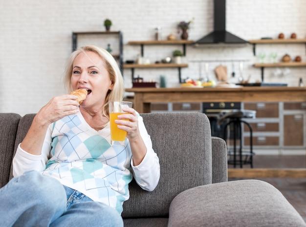 Coup moyen femme manger sur le canapé