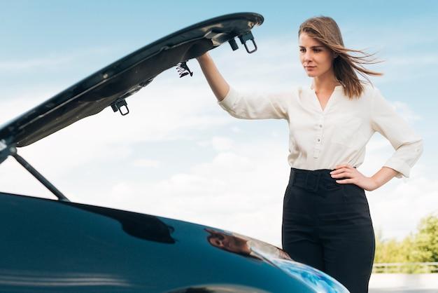 Coup moyen d'une femme ouvrant le capot d'une voiture