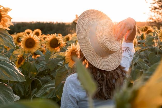 Coup moyen femme portant un chapeau dans le champ