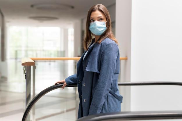 Coup moyen femme portant un masque à l'intérieur