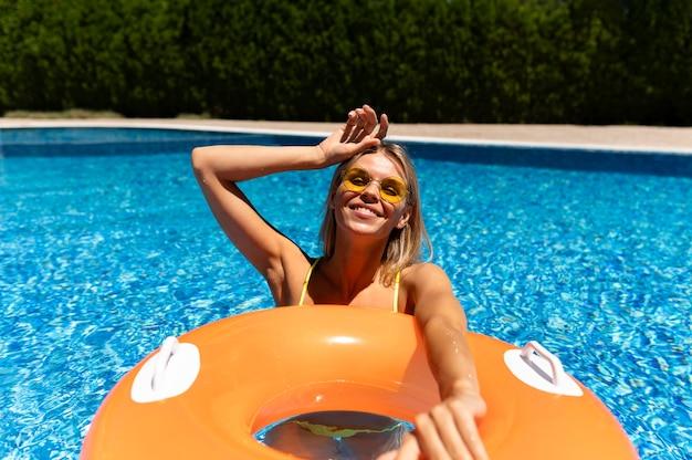 Coup moyen femme posant avec bouée de sauvetage