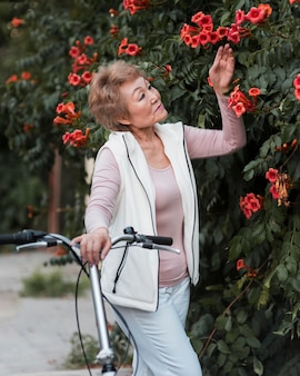 Coup moyen femme posant avec des fleurs