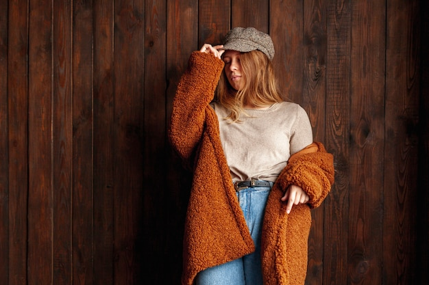 Coup moyen femme posant avec fond en bois