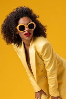 Coup moyen femme posant avec des lunettes de soleil jaunes