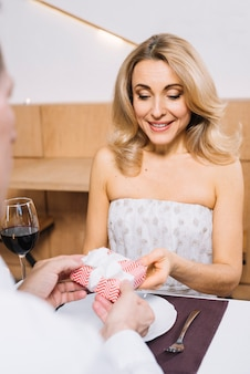Coup moyen d'une femme qui reçoit un cadeau pendant le dîner