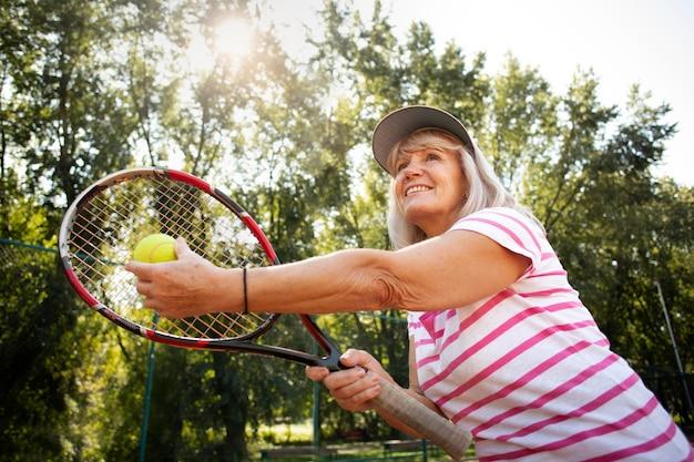 Coup moyen femme senior jouant au tennis