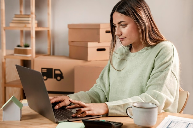 Coup moyen femme tapant sur ordinateur portable