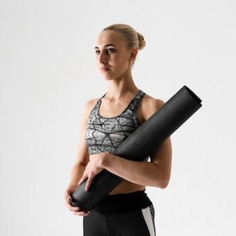 Coup moyen femme avec tapis de yoga noir