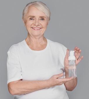 Coup moyen femme tenant une bouteille de sérum