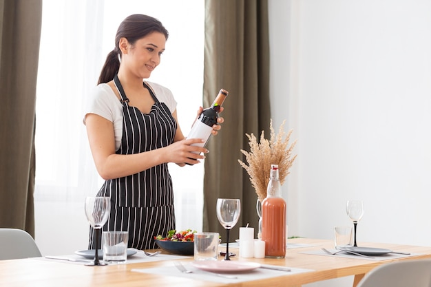 Coup moyen femme tenant une bouteille de vin