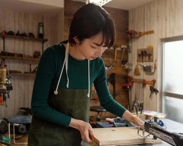Coup moyen femme tenant un morceau de bois