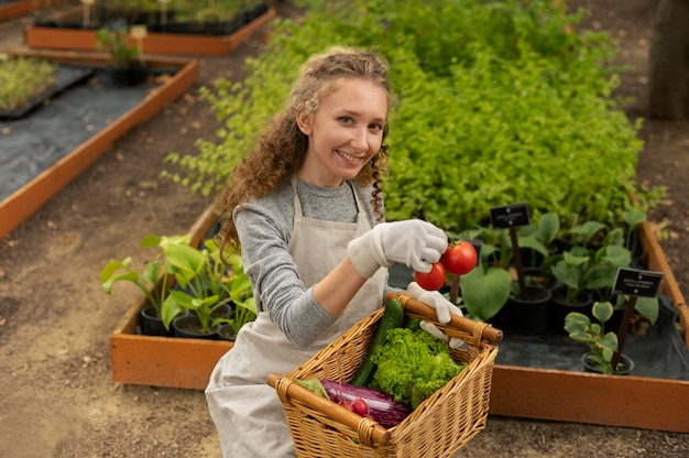Coup moyen femme tenant un panier de légumes