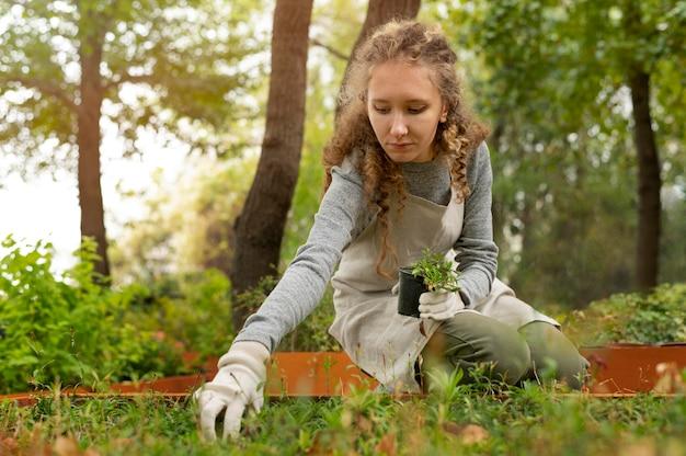 Coup moyen femme tenant un pot de plante