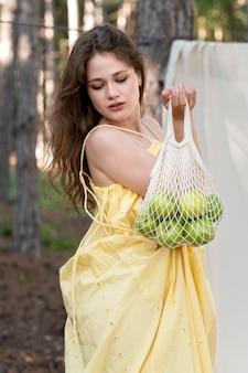 Coup moyen femme tenant un sac durable