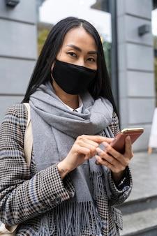 Coup moyen femme tenant un smartphone