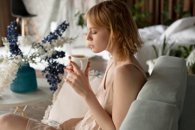 Coup Moyen Femme Tenant Une Tasse De Café Photo gratuit