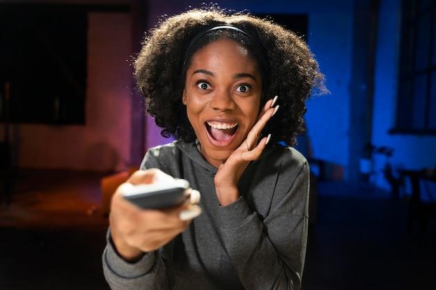 Coup moyen femme tenant la télécommande