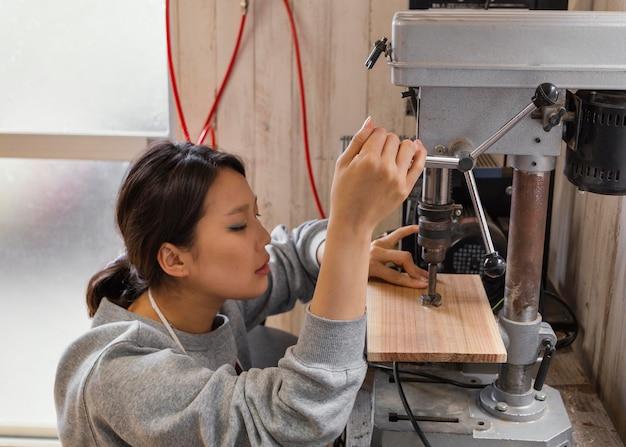 Coup moyen femme travaillant avec machine