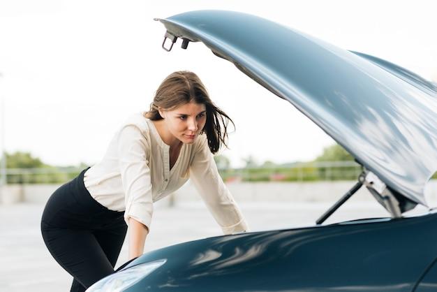 Coup moyen de femme vérifiant le moteur