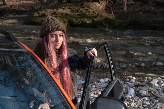 Coup moyen femme avec voiture à l'extérieur