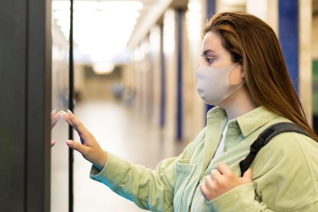 Coup moyen femme voyageant avec masque