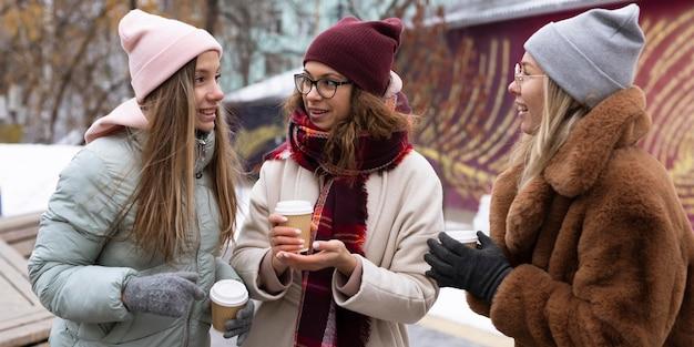 Coup moyen des femmes avec du café à l'extérieur