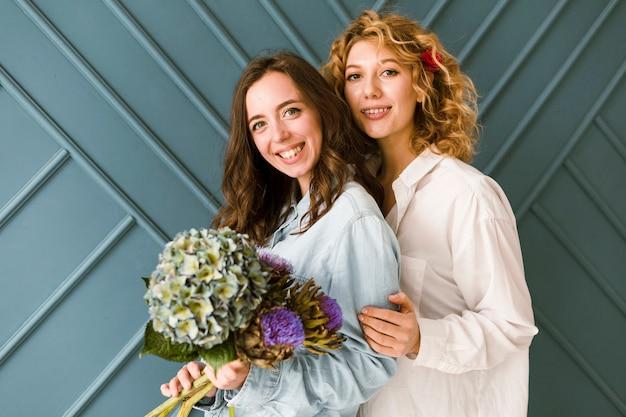 Coup moyen femmes heureuses avec bouquet à l'intérieur