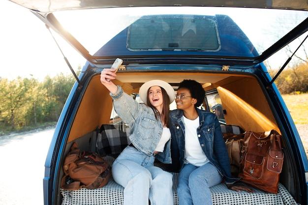 Coup moyen femmes heureuses prenant selfie